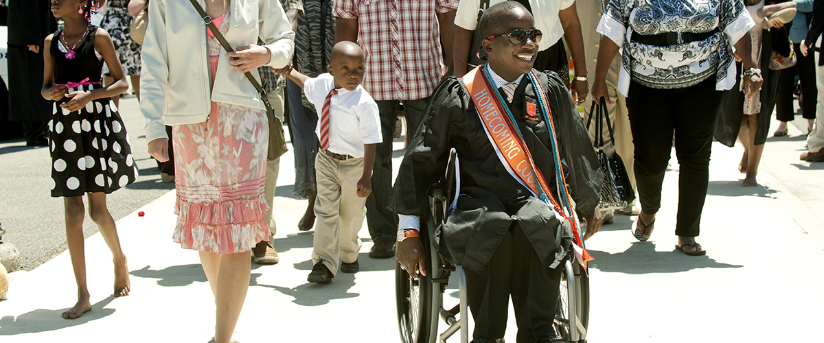 a student moves towards Commencement in his wheelchair